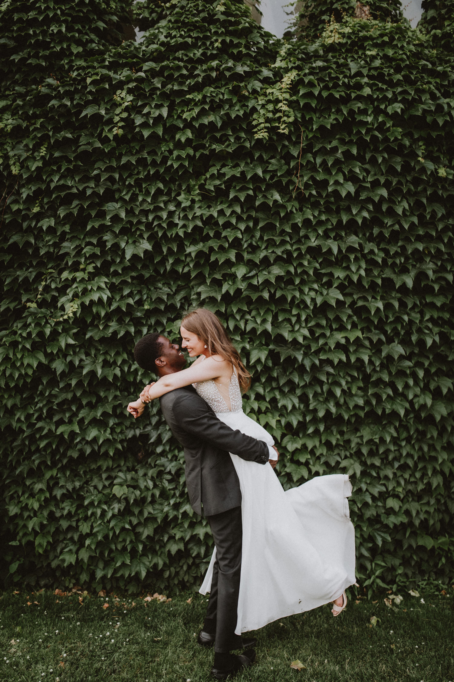 Adorable couple wedding photography at University of Toronto by a wall greeneries